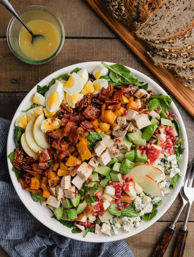 overhead of a fall harvest cobb salad in a white bowl next to a jar of maple dijon vinaigrette and a board of whole grain bread
