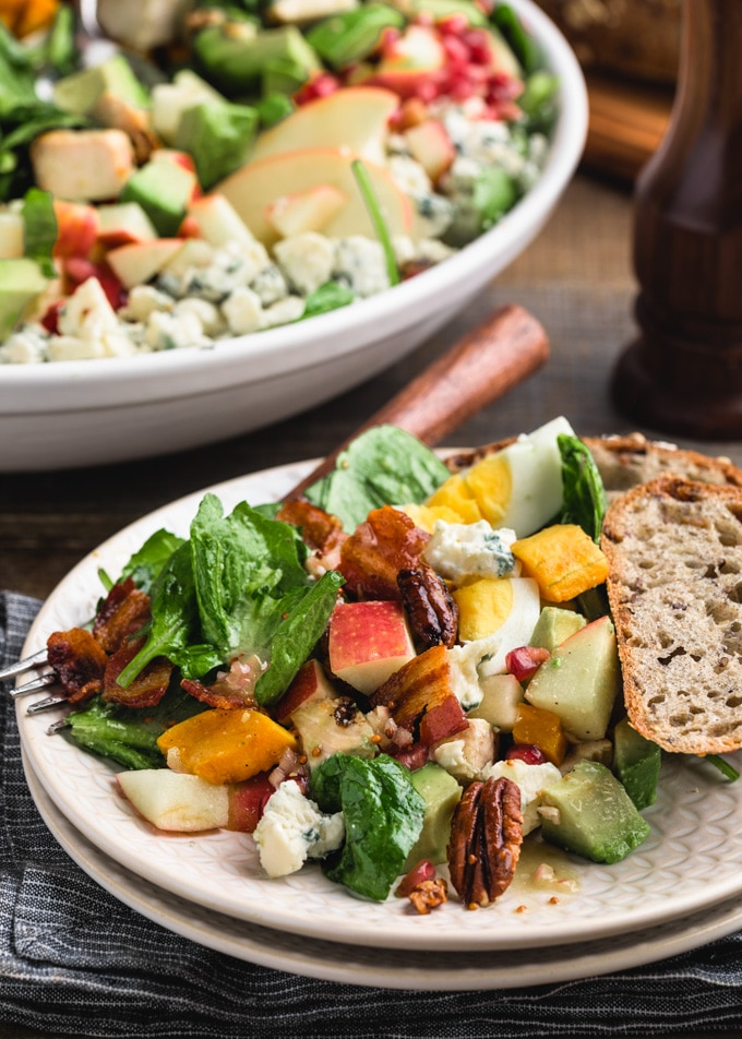 side view of a Cobb salad with apples, pecans, and butternut squash on an ivory plate with whole grain bread
