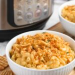 instant pot macaroni and cheese in a white bowl with crushed cheese crisps