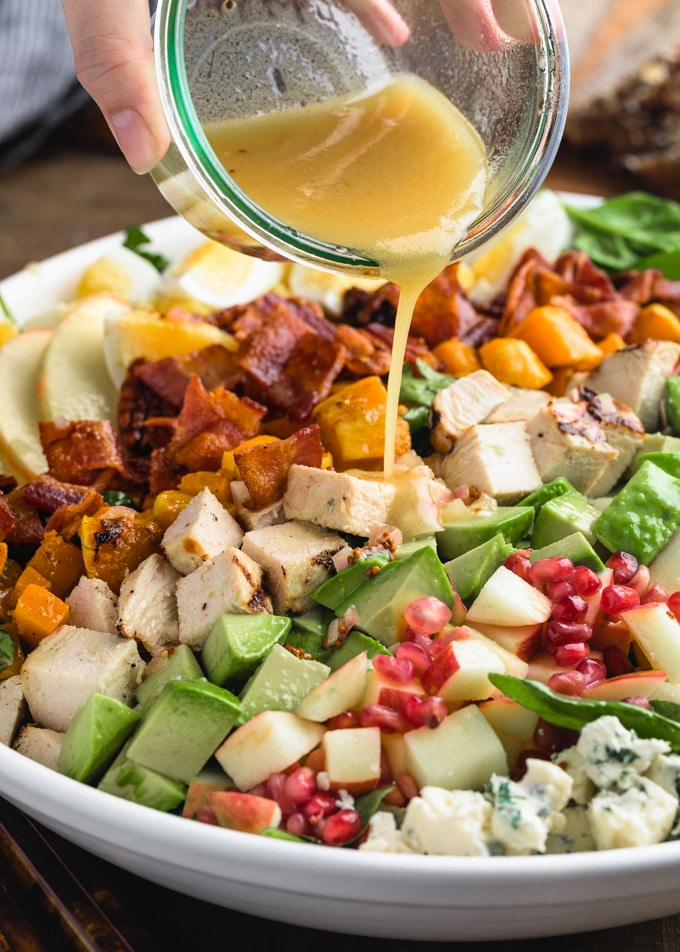 pouring Maple-Dijon Vinaigrette onto a harvest Cobb Salad