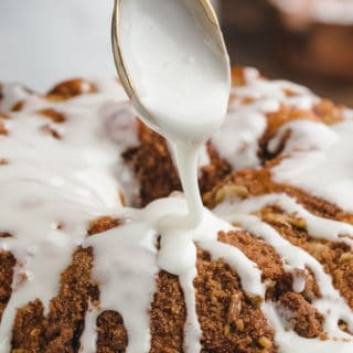 closeup of powdered sugar glaze being drizzled onto a coffee cake from a gold spoon