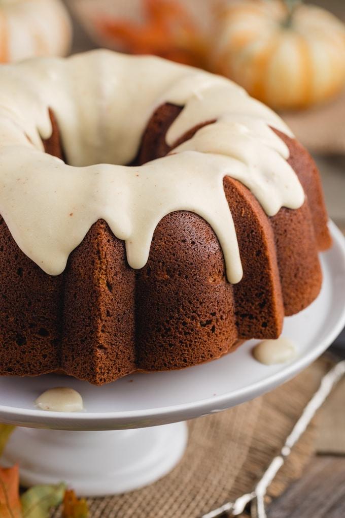 glazed pumpkin bundt cake on a white cake pedestal with autumn decorations (pumpkins, leaves)