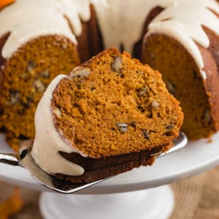 slice of pumpkin bundt cake on a cake server in front of the full cake on a white pedestal