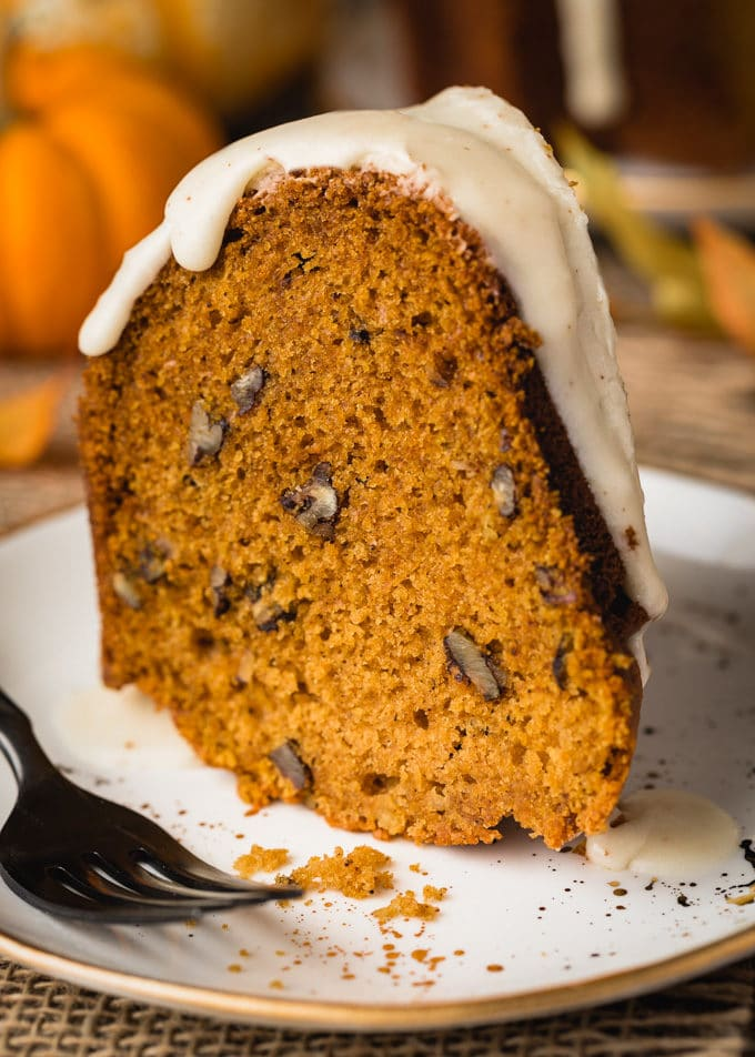 side view of a slice of pumpkin pecan bundt cake on a white plate with a black fork