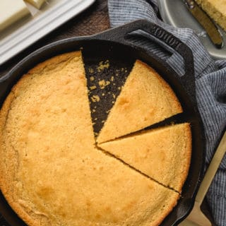 overhead of buttermilk cornbread sliced into wedges in a cast iron skillet