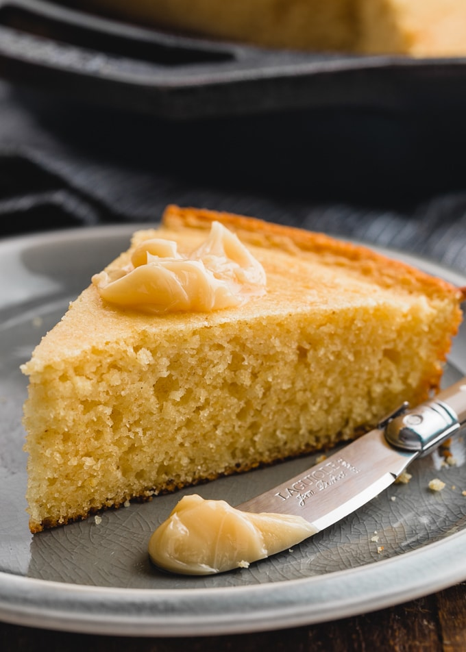 slice of sour cream cornbread on a plate with a dollop of maple butter