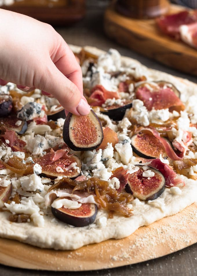 placing a sliced fresh fig onto an unbaked pizza