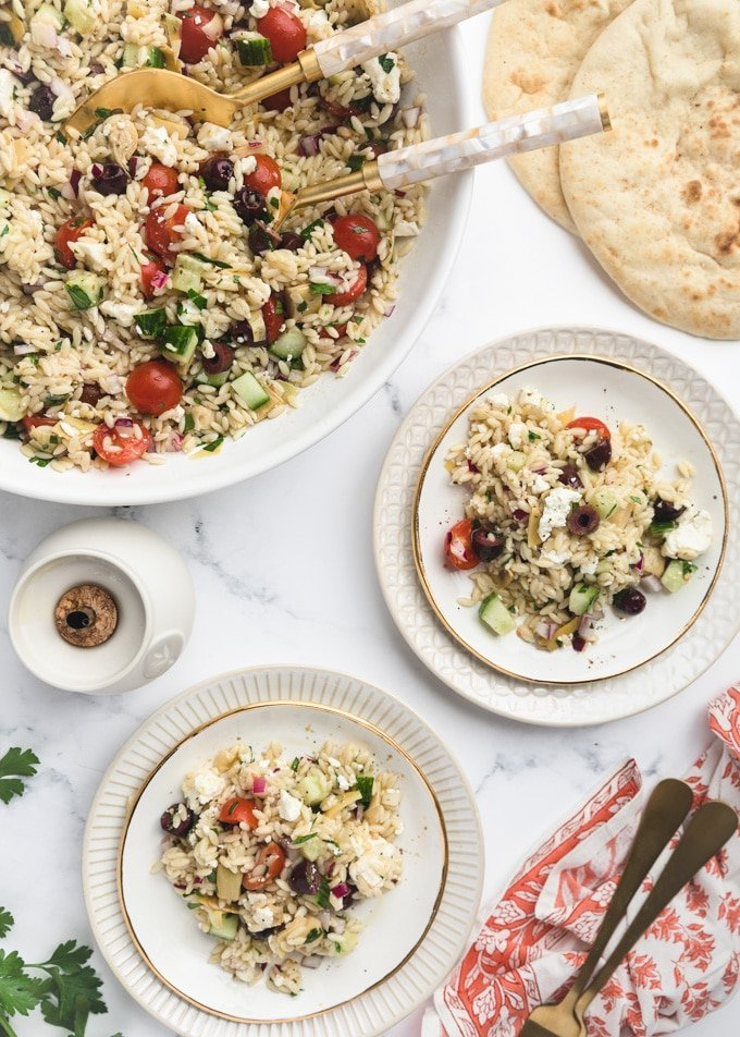 overhead of orzo salad served on white plates, next to a big bowl of the salad and pita bread rounds