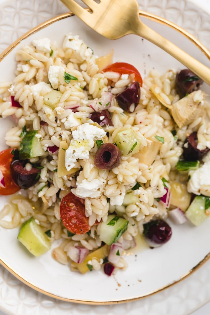 overhead closeup of orzo pasta salad with Feta cheese and kalamata olives on a white and gold plate