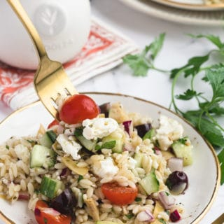 greek orzo salad on a white and gold plate, being scooped up with a gold fork