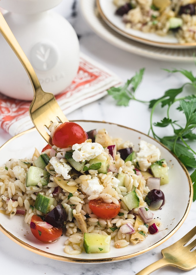 orzo salad on a white and gold plate, being scooped up with a gold fork
