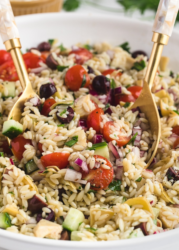 closeup of orzo salad being tossed with a gold salad spoon set