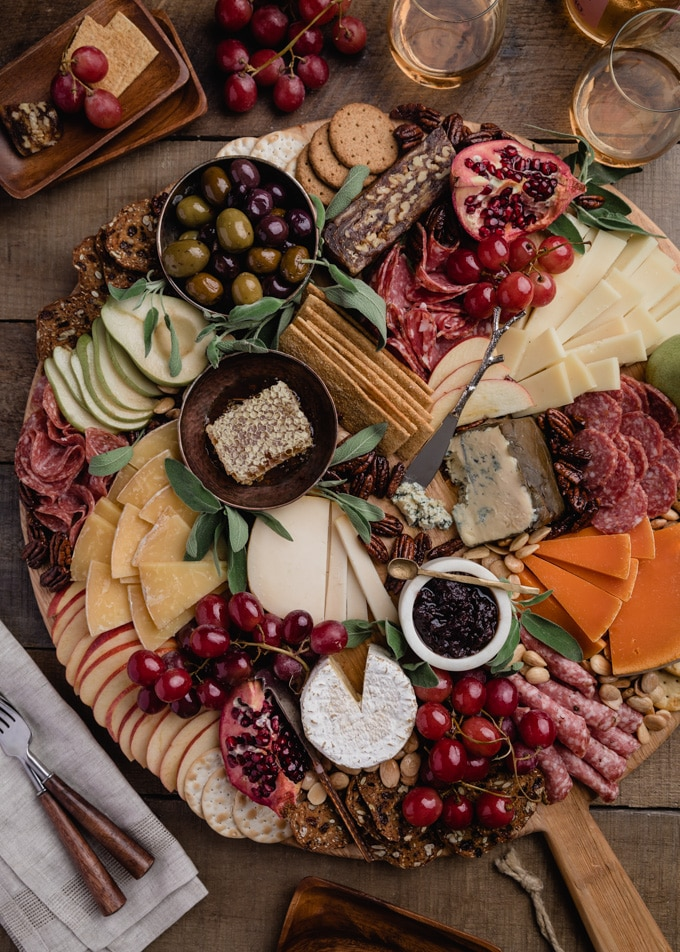 overhead of a fall cheese board on a large round pine charcuterie board