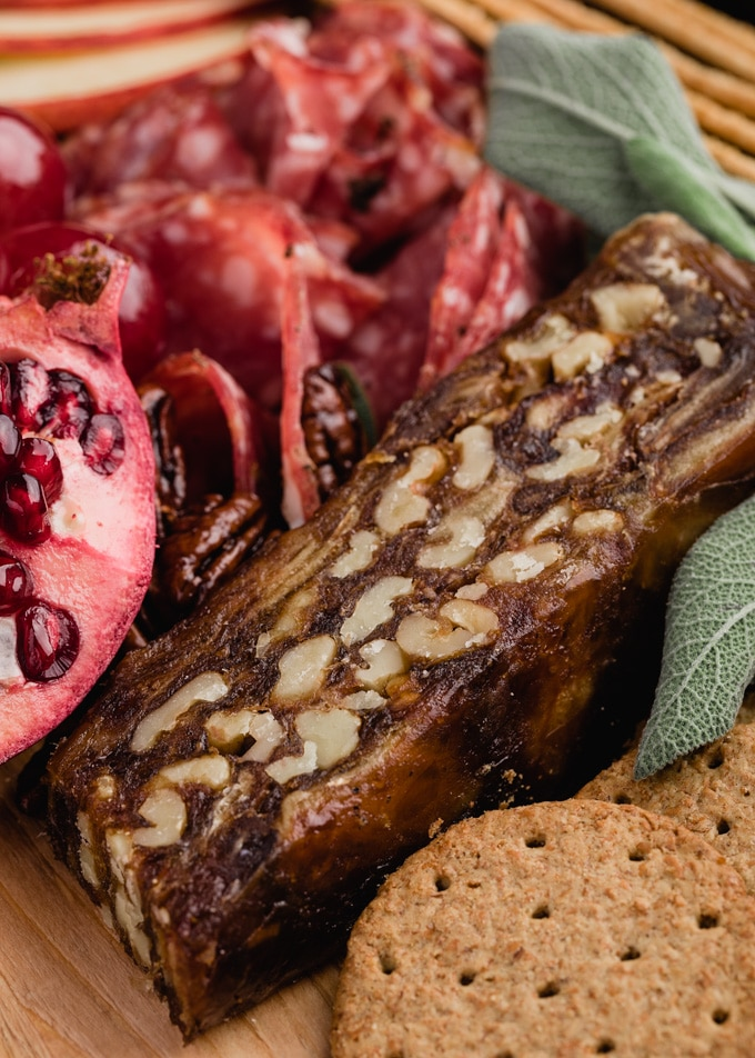 Slice of Spanish date and walnut cake next to pomegranates and charcuterie