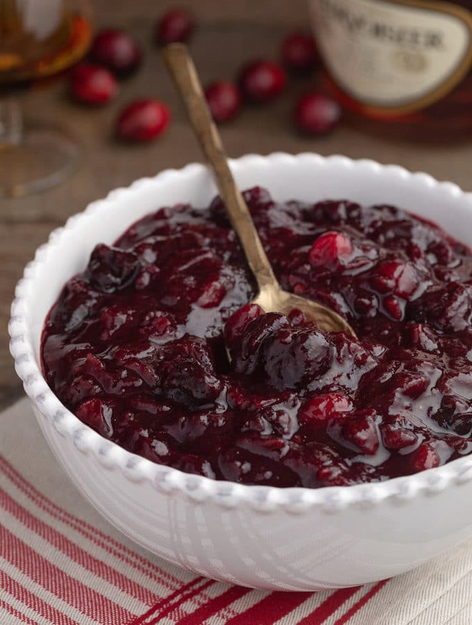 brandied cherry cranberry sauce in a white bowl with a gold spoon