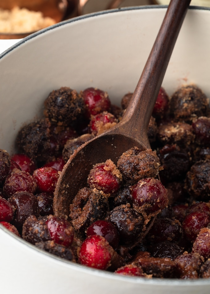 cranberries and cherries tossed with brown sugar and spices on a wood spoon in a white pot