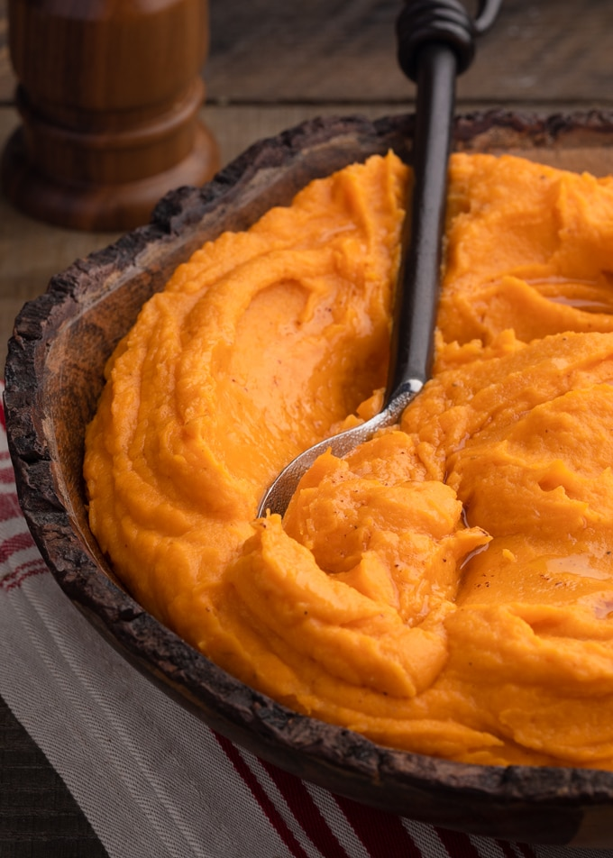 brown butter whipped sweet potatoes in a wooden bowl with a serving spoon