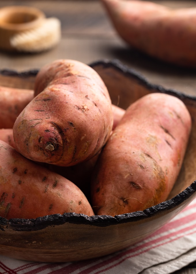 raw sweet potatoes in a large wooden bowl on a beige and red napkin