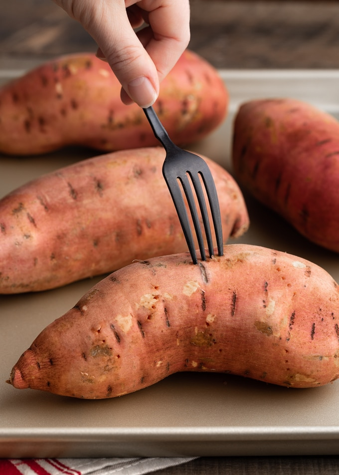 fork piercing raw sweet potatoes on a baking sheet