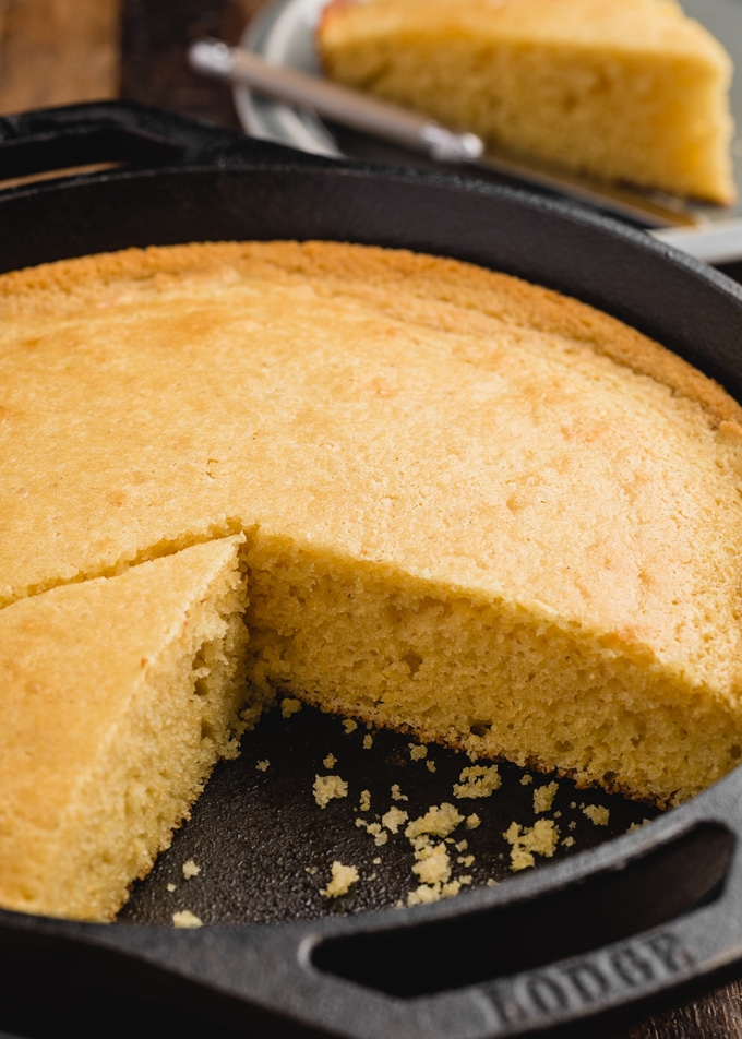 side view of baked sweet cornbread in a cast iron skillet