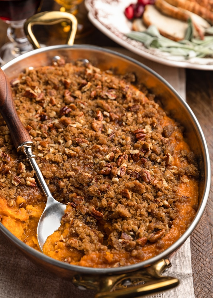 buttermilk sweet potato casserole in a copper gratin dish with a serving spoon