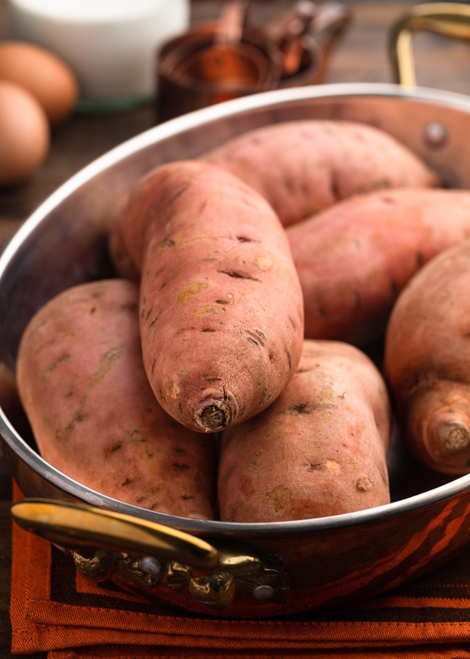 uncooked sweet potatoes piled into a copper baking dish