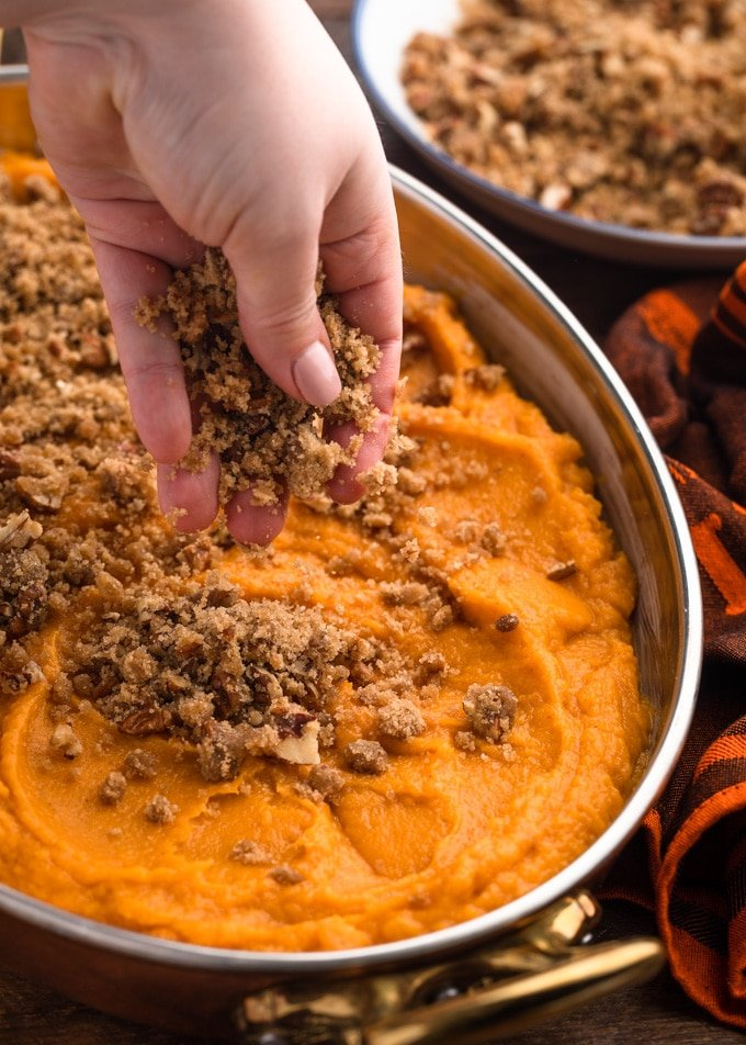 sprinkling pecan streusel topping over an unbaked sweet potato casserole