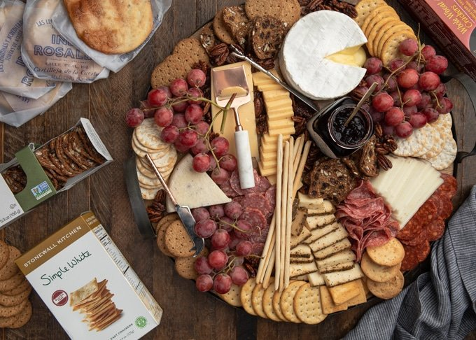 assembled cheese board next to boxes of artisan crackers