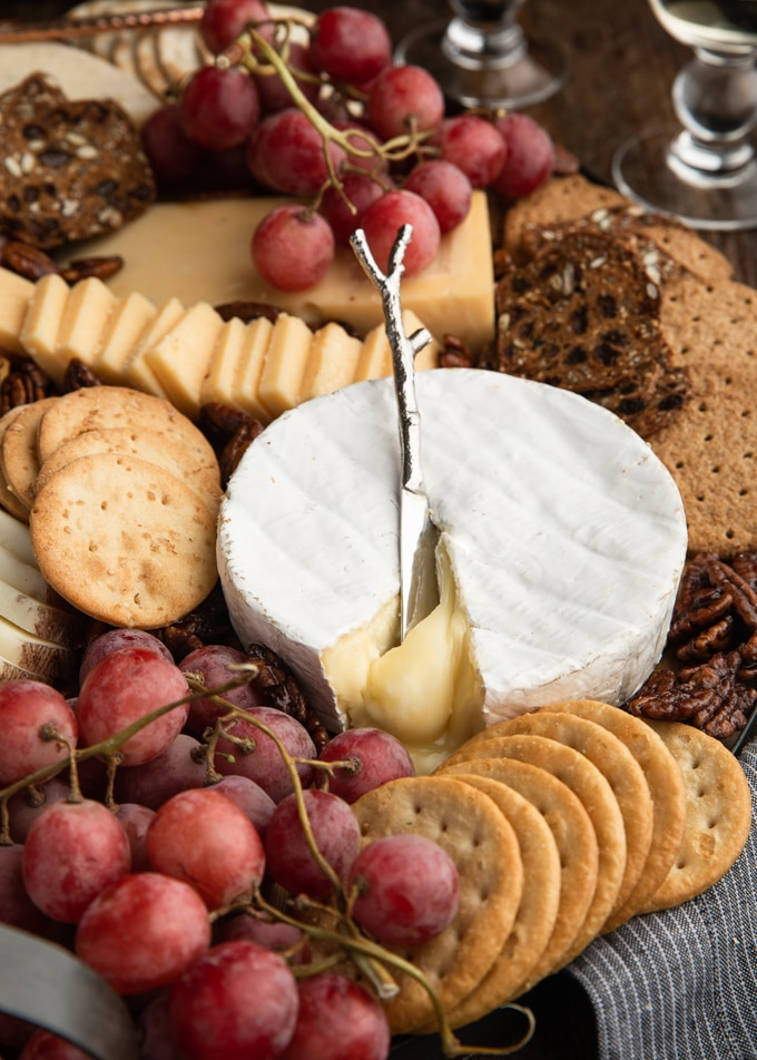assorted crackers and cheeses with grapes on a wood board