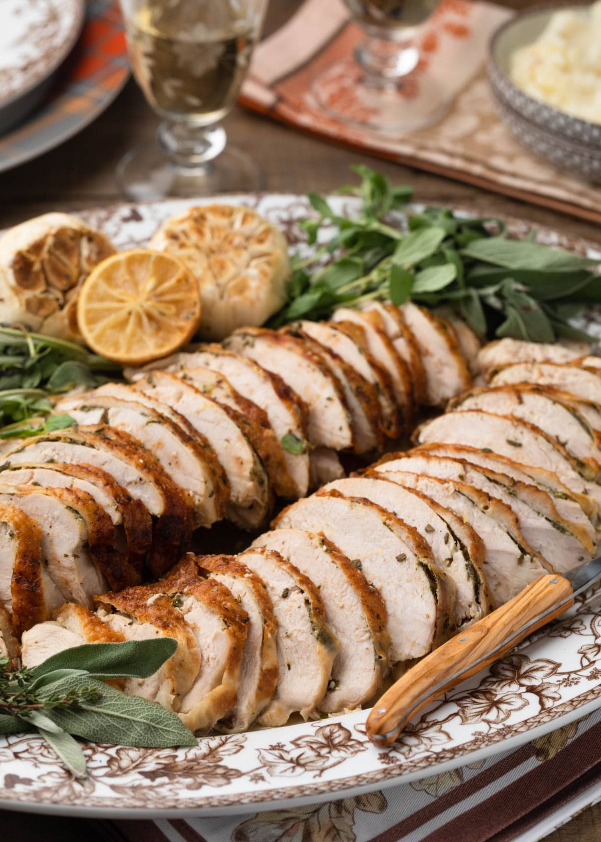 slices of herb roasted turkey breast on a platter with herbs, roasted lemon, and garlic