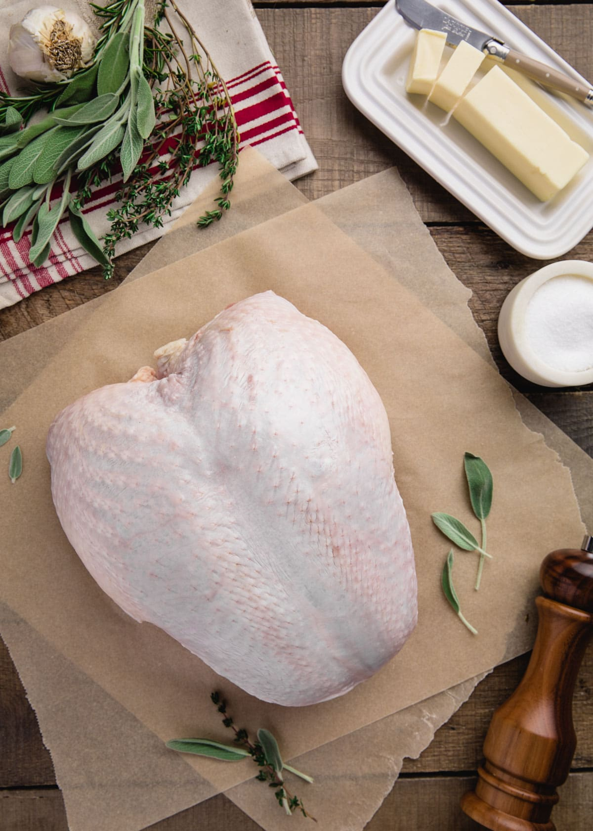raw whole turkey breast on parchment paper next to a stick of butter, herbs, and seasonings