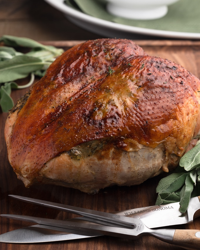 herb roasted turkey breast resting on a carving board