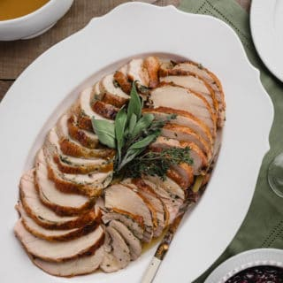 herb roasted turkey breast sliced and served on a white platter