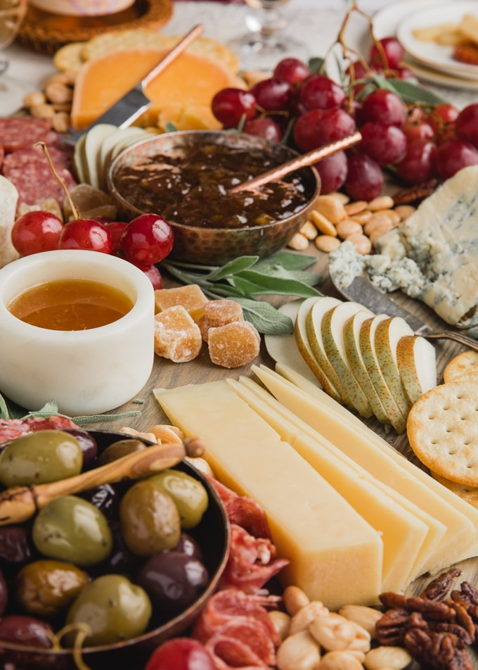 side view of a cheese board with assorted charcuterie, nuts, honey, fruit, and preserves