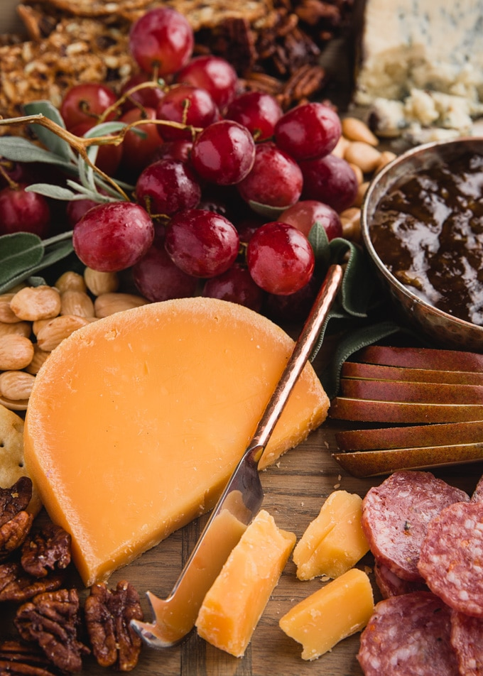 wedge of aged gouda on a cheese board with grapes, pears, charcuterie, and nuts