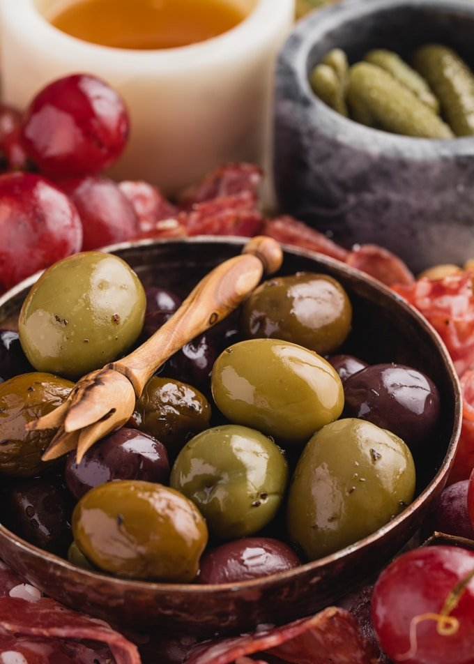bowl of olives, honey, and cornichons with charcuterie and fruit on a cheese board
