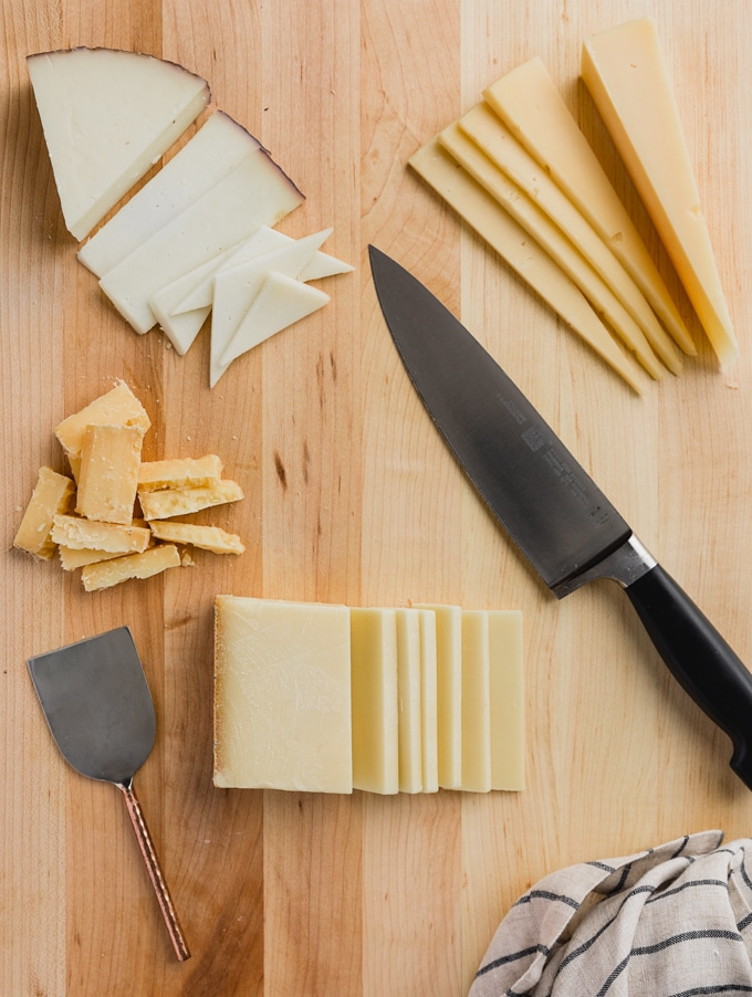 sliced blocks of cheese on a wood cutting board with a chef's knife and a cheese knife