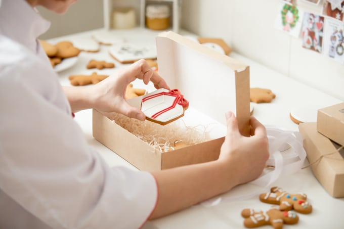 woman packing Christmas cookies in a paper box filled with shredded paper crinkles