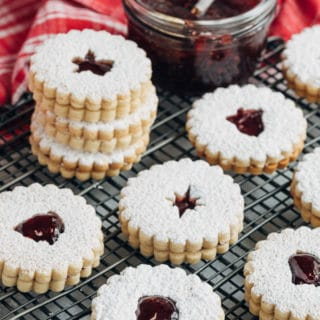 raspberry jam filled linzer cookies on a wire cooling rack