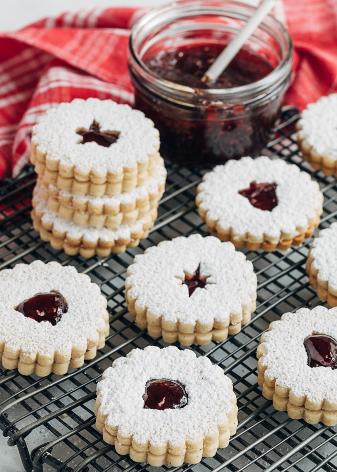 linzer cookies with raspberry jam on a cooling rack