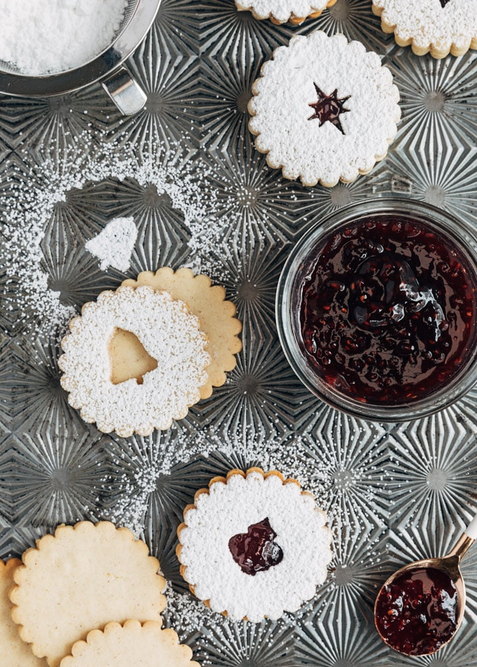 unassembled and assembled linzer cookies on a baking sheet, dusted with powdered sugar