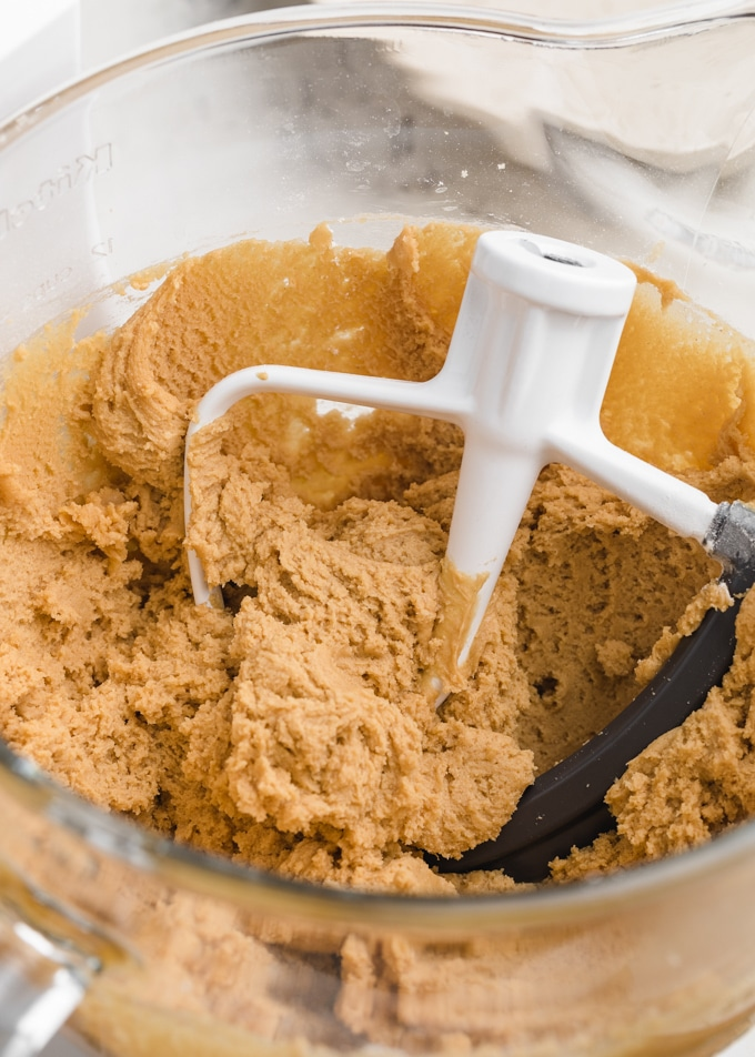peanut butter blossom dough in the glass bowl of a stand mixer with the paddle attachment