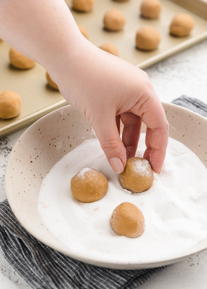 rolling balls of peanut butter cookie dough in granulated sugar in a ceramic bowl