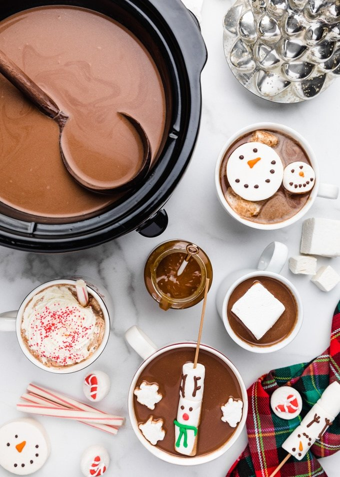 hot chocolate in a crockpot with a ladle, surrounded buy mugs of hot chocolate with snowman and reindeer marshmallows