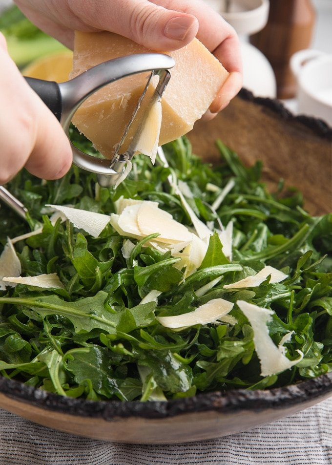 wedge of parmigiano reggiano being shaved over arugula salad