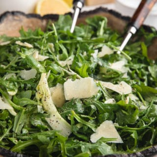 arugula salad with shaved fennel and parmigiano reggiano in a wooden serving bowl