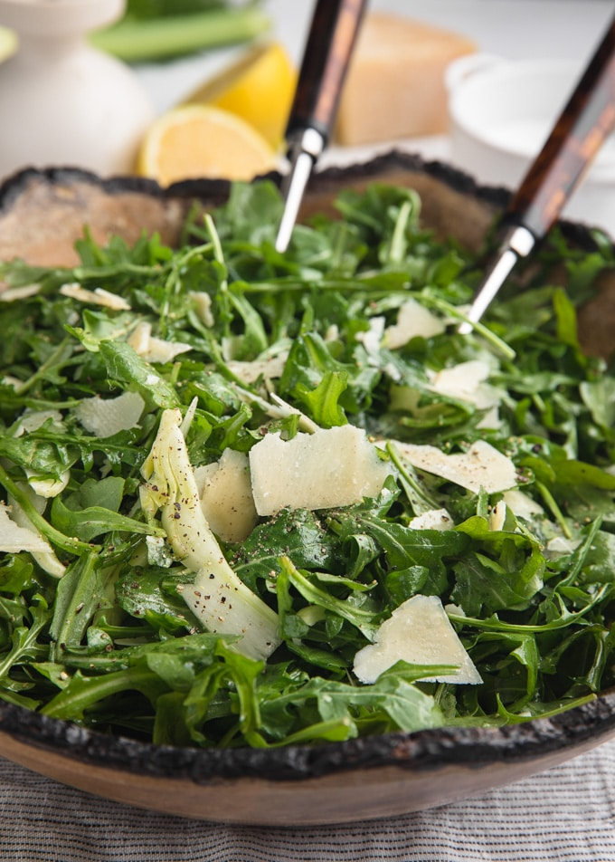 arugula salad with fennel and shaved parmigiano reggiano in a wood bowl with salad servers