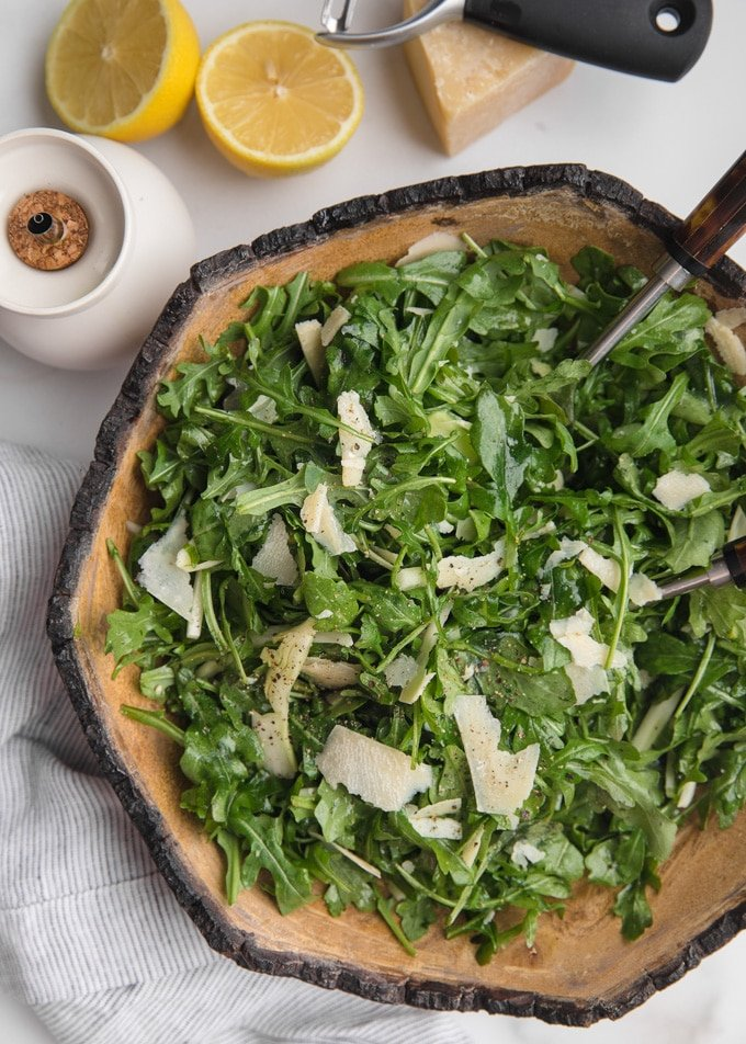 overhead of arugula and shaved fennel salad in a wood bowl