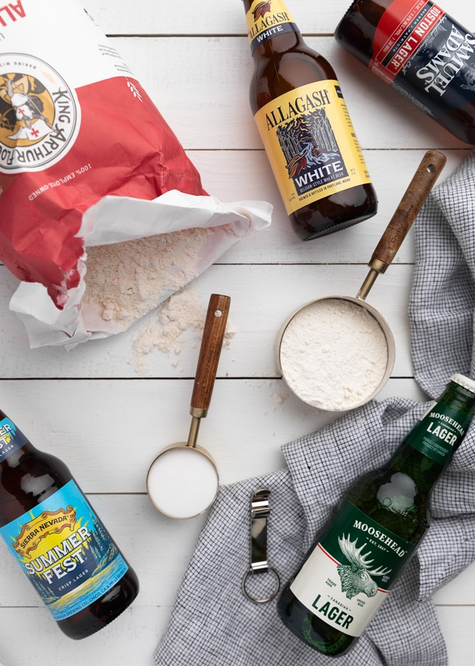 flatlay showing an open bag of all purpose flour, measuring cups filled with flour and sugar, and 5 different bottles of beer