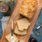 sliced beer bread loaf on a wood serving board with butter and honey